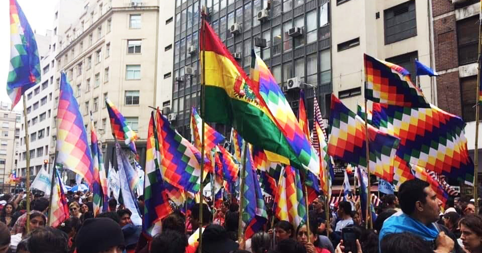 Photo of a Bolivian flag and numerous Pachamama flags.