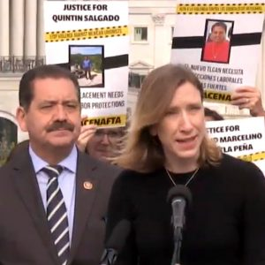"""Sister Quincy Howard speaking into a microphone with Congressman Chuy Garcia next to her and a placard reading """"Justice for Quintin Salgado"""" behind them."""